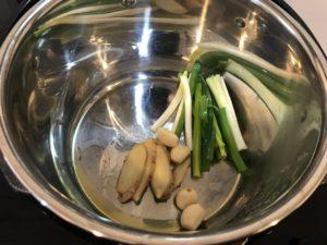 取一滷鍋,加熱,放油,把青蔥、薑、蒜頭放入炒香