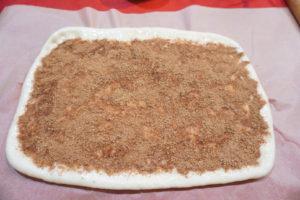 在麵團上塗上適量椰子油,再撒上滿滿的砂糖與肉桂粉,上面預留0.6公分以便捲起。